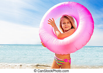 Beautiful little girl with swim ring on the beach