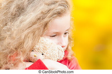 Beautiful and sad little girl hugging teddy bear. Looking away from the camera. Yellow autumn trees in background.