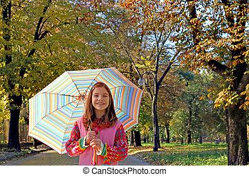 beautiful little girl with umbrella autumn season