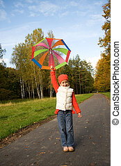 Beautiful little girl with umbrella in a forest