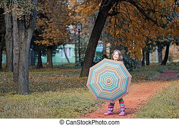 beautiful little girl with umbrella in park autumn season