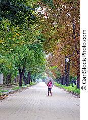 beautiful little girl with umbrella on street autumn season