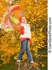 Beautiful little girl with umbrella outdoors