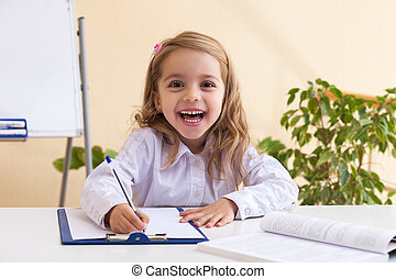 Beautiful little girl writes sitting at table