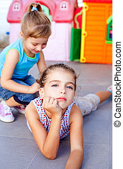 beautiful little little girls lying on playground floor