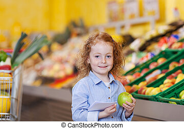 Beautiful little redhead girl with an apple