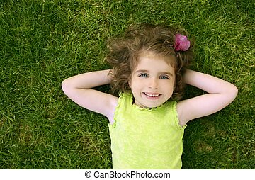 Beautiful little toddler girl happy lying on grass - ...