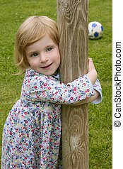 Beautiful little toddler girl hug a trunk