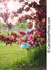 Beautiful Little Toddler Girl Standing Under Flowering Crabapple Tree Smiling
