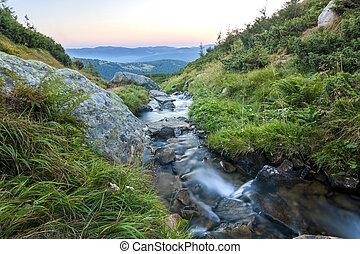 Beautiful little waterfall in mountains with white foamy silky water