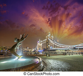 Beautiful London sunset. Dolphin fountain and magnificent Tower