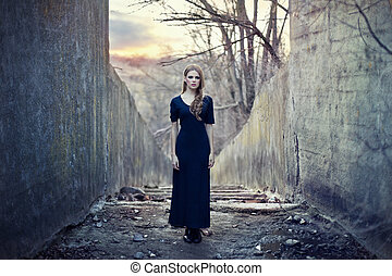 beautiful lonely girl in long dress near gloomy tunnel on...