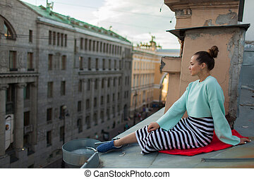 Beautiful lonely girl sitting on the roof in the old town of dreams.