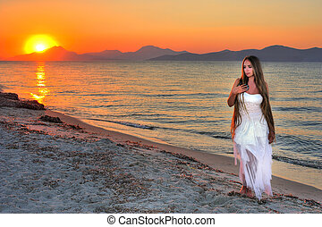 Beautiful lonely girl on the seashore