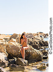 Beautiful long hair female model wearing bikini, posing  outdoor portrait
