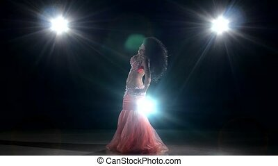 Beautiful, long-haired belly dancer girl dancing exotic dance movement on black, back light