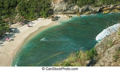 Beautiful long white ocean waves rolling to the sandy Atuh beach. Clear pure transparent water in the lagoon, Nusa Penida, Bali, Indonesia
