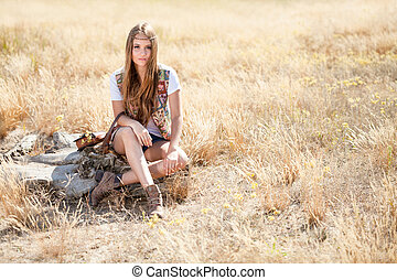 Beautiful longhair hippie girl sitting on a tree stump