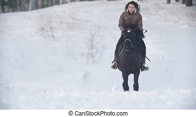 Beautiful longhaired female rider wild and fast riding black...