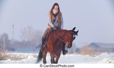 Beautiful longhaired woman riding a brown horse through the...