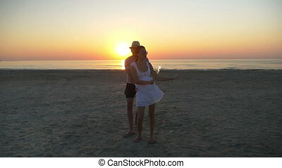 Beautiful lovers dancing on the beach with a firework candle at sunset