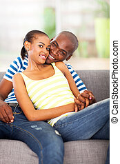 loving african american couple sitting on the couch