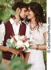 Beautiful loving couple dressed in boho chic style
