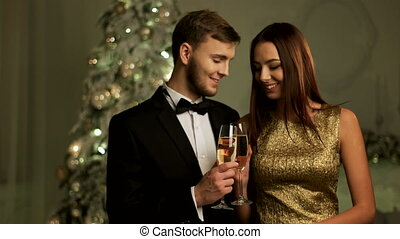 Beautiful loving couple holding glasses of champagne and celebrating Happy New Year day.