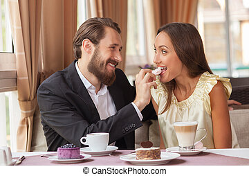 Beautiful loving couple is eating in restaurant