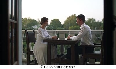 Beautiful loving couple sitting at a table in a restaurant outdoors on their wedding day.