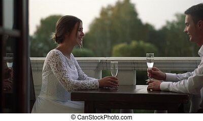 Beautiful loving couple sitting at a table in a restaurant outdoors on their wedding day