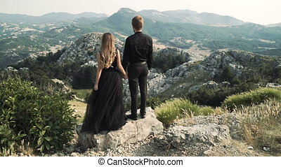 beautiful loving couple young woman model in a smart long dress and a man in a black suit posing on the camera against a backdrop of a mountain landscape.
