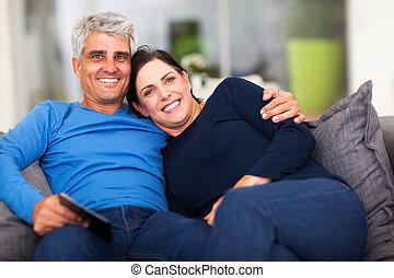 beautiful loving middle aged couple sitting on sofa