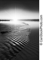 Beautiful low point of view along beach at low tide out to sea with vibrant sunrise sky black and white