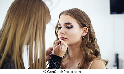 Beautiful Make-up artist applying makeup to a model in the...