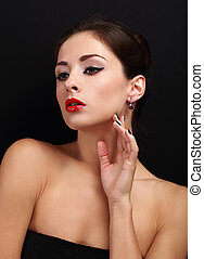 Beautiful makeup calm woman with red lipstick and earrings on black
