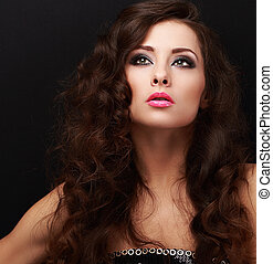 Beautiful makeup fashion model looking up with smokey eyes makeup on black. Closeup