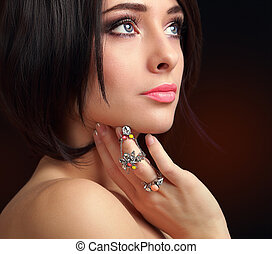 Beautiful makeup female face with ring on finger. Closeup portrait