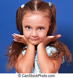 Beautiful makeup kid girl posing in dress with hands under face on blue background. Closeup portrait
