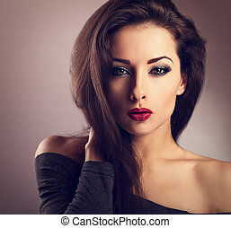 Beautiful makeup sexy woman with hot red lipstick and long eye lashes looking expression. Vintage toned closeup portrait