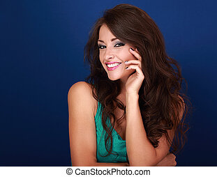Beautiful makeup smiling woman with curly long brown hair with manicured nails on blue background