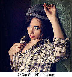 Beautiful makeup teen girl in trendy black and white checkered shirt and blue summer cap thinking on blue wooden doors background looking down. Short hairstyle.