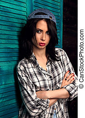 Beautiful makeup teen girl in trendy black and white checkered shirt and blue summer cap thinking on blue wooden background with folded arms. Short hairstyle