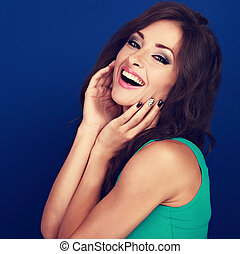 Beautiful makeup toothy laughing woman with curly long brown hair and manicured nails on blue background