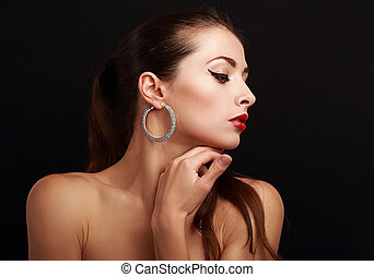 Beautiful makeup woman face profile in fashion earrings. Eyeliner black makeup eyes on black background with empty copy space