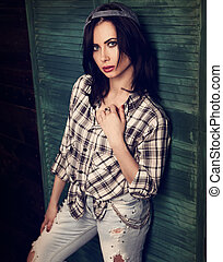 Beautiful makeup woman in trendy black and white checkered shirt and blue ripped jeans looking sexy on blue wooden doors background. contrast closeup fashion portrait. Toned color