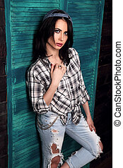 Beautiful makeup woman in trendy black and white checkered shirt and blue ripped jeans