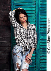 Beautiful makeup woman in trendy black and white checkered shirt and blue ripped jeans thinking and looking down on blue wooden background. Short hairstyle. contrast closeup portrait.