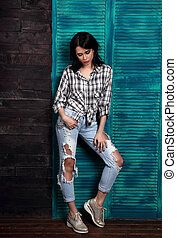 Beautiful makeup woman in trendy black and white checkered shirt, blue ripped jeans, fashion shoes thinking and looking down on blue wooden background.