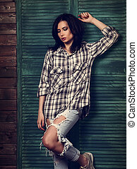 Beautiful makeup woman in trendy black and white checkered shirt, blue ripped jeans thinking and looking down on blue wooden doors background. Toned portrait